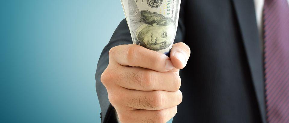 Businessman hand grabbing money, US dollar (USD) bills