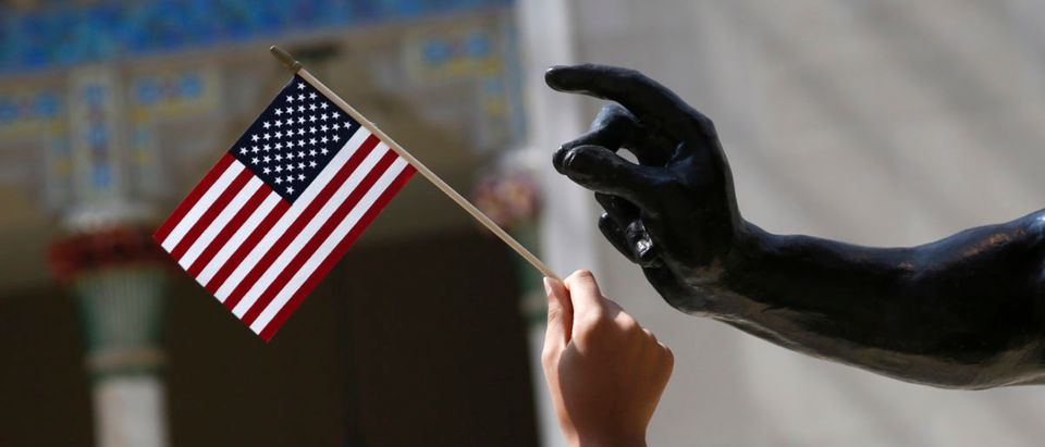 A girl holds a U.S. flag next to a sculpture after a naturalization ceremony at The Metropolitan Museum of Art in New York
