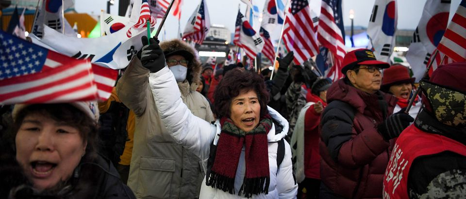Anti North Korean protestors hold Unified Korean flags with a red cross outside the stadium before the opening ceremony of the Pyeongchang 2018 Winter Olympic Games at the Pyeongchang Stadium on February 9, 2018. / AFP PHOTO / Ed JONES (Photo credit should read ED JONES/AFP/Getty Images)