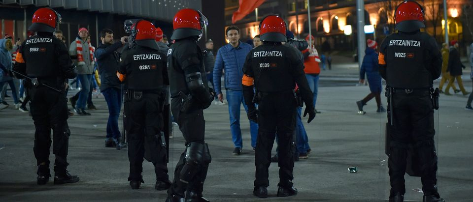 Spartak fans walk past Basque autonomous police officers outside the San Mames stadium after the Europa League Round of 32 second leg football match between Athletic Club Bilbao and FC Spartak Moscow at the San Mames stadium in Bilbao on February 22, 2018. A Basque police officer died on February 22, 2018 as security forces clashed with fans of Russian club Spartak Moscow in the Spanish city of Bilbao where a Europa League match was taking place. (ANDER GILLENEA/AFP/Getty Images)