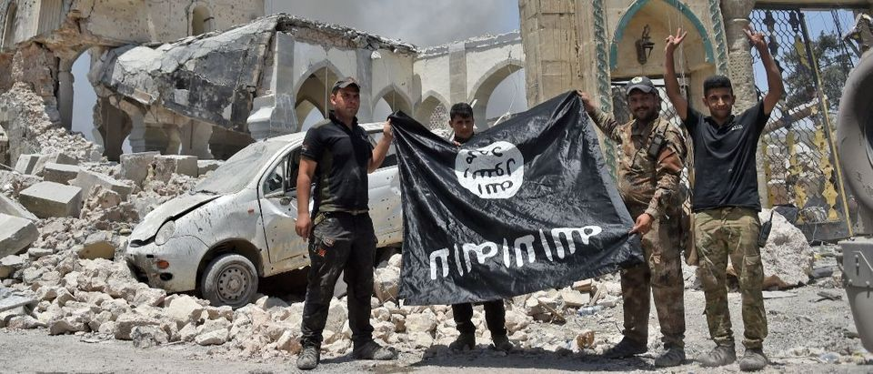 ISIS fighres hold the Islamic State flag (AFP/Getty Images/Fadel Senna)