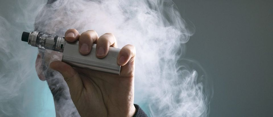 Young man vape electronic cigarette cloud by using a mod, smoke tricks of vaping device background. (Hazem.m.kamal/Shutterstock)