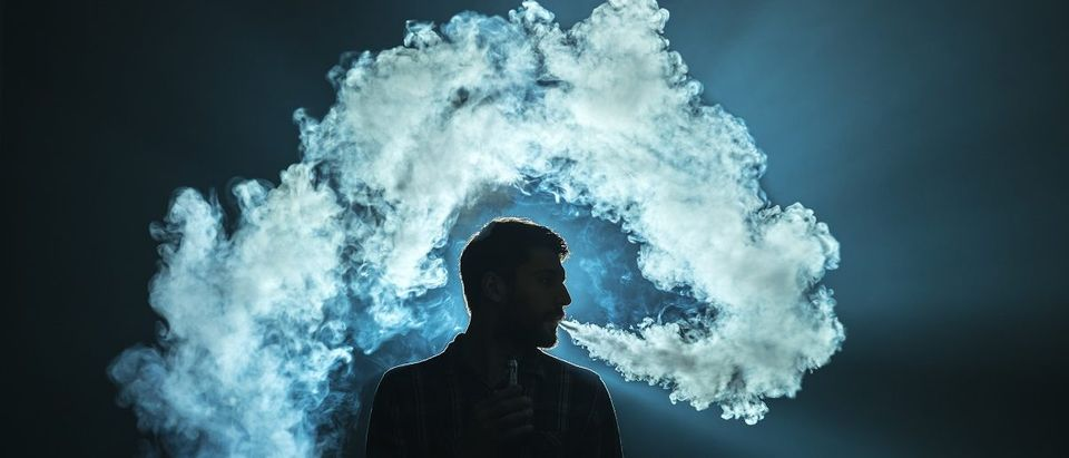The man smoke an electronic cigarette on the dark background. (Realstock/Shutterstock)