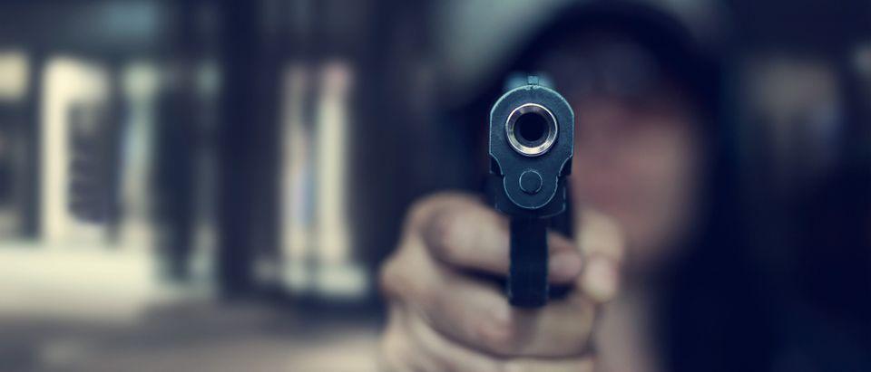 A hooded an holds up a gun. (Shutterstock)