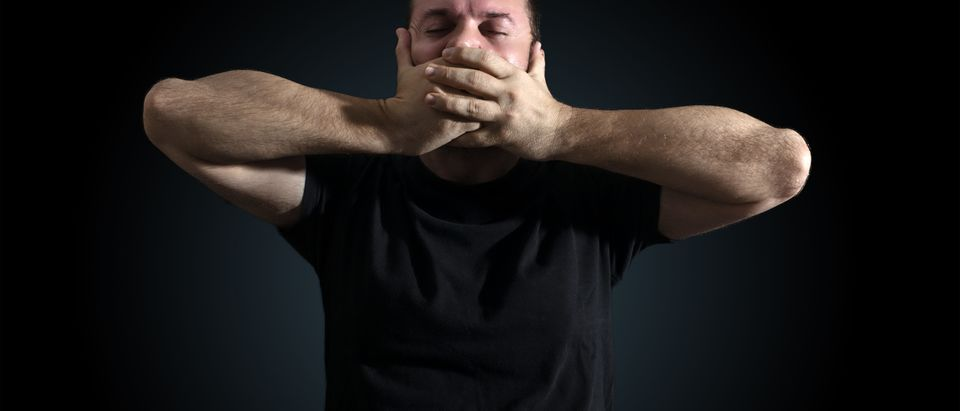 A man with his hands over his mouth. Shutterstock