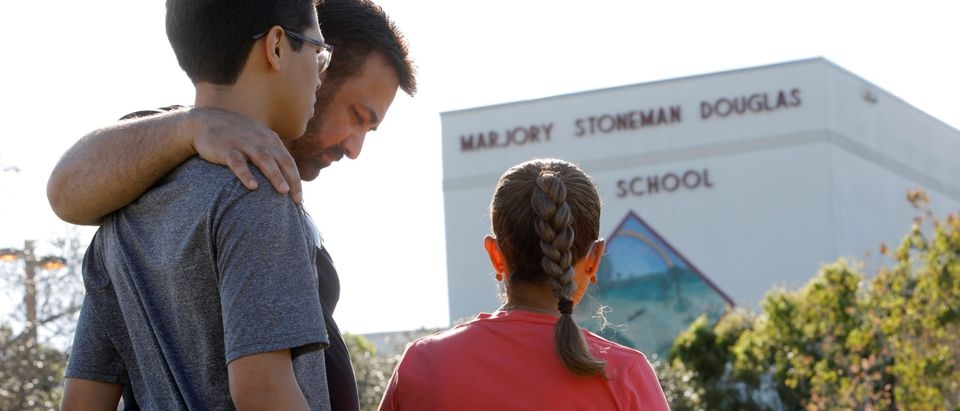 A father and his two children share a moment of reflection at Marjory Stoneman Douglas High School four days after the shooting there, in Parkland