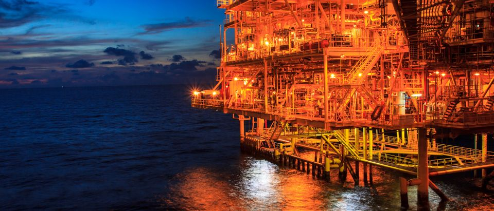 The large offshore oil rig at night with twilight background. (Shutterstock)