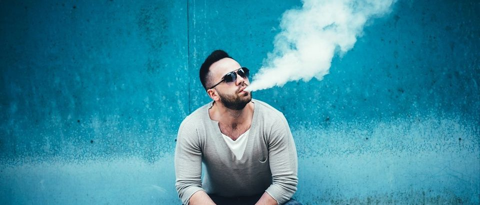 Men with beard vaping outdoor in sunglasses. (bedya/Shutterstock)