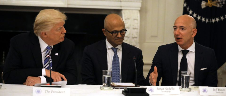 U.S. President Donald Trump and Satya Nadella CEO of Microsoft Corporation listen as Jeff Bezos, CEO of Amazon speaks during an American Technology Council roundtable at the White House in Washington, U.S.