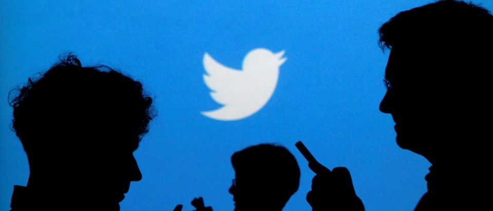 FILE PHOTO - People holding mobile phones are silhouetted against a backdrop projected with the Twitter logo in Warsaw