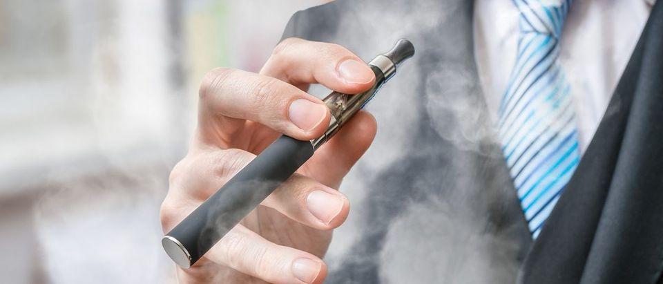 Businessman holds vaporizer. (vchal/Shutterstock)