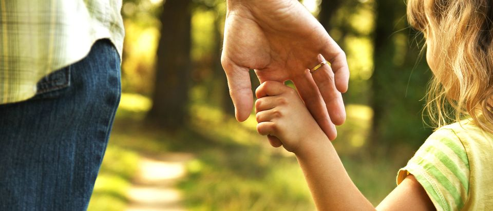 Parent holds child's hand Shutterstock