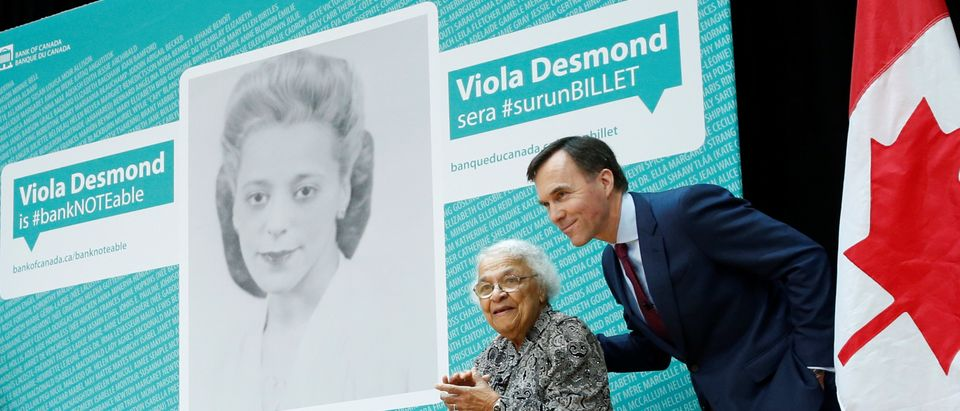 Canada's Finance Minister Bill Morneau stands with Wanda Robson after her sister Viola Desmond was chosen to be featured on a new $10 bank note in Gatineau
