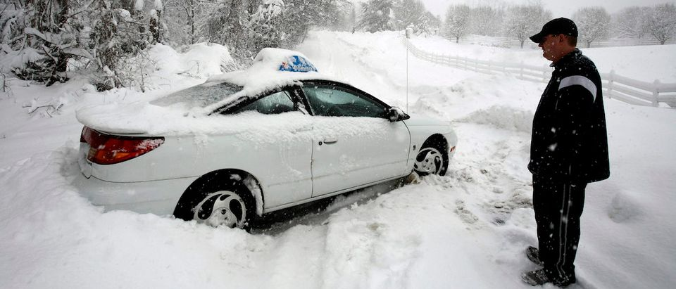 A Domino's Pizza delivery man ponders his next move after his vehicle got stucked on a snow-covered road in Great Falls
