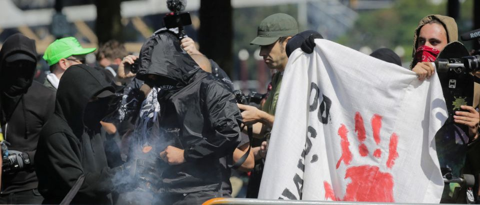 Antifa counter protesters light a smoke grenade in Portland