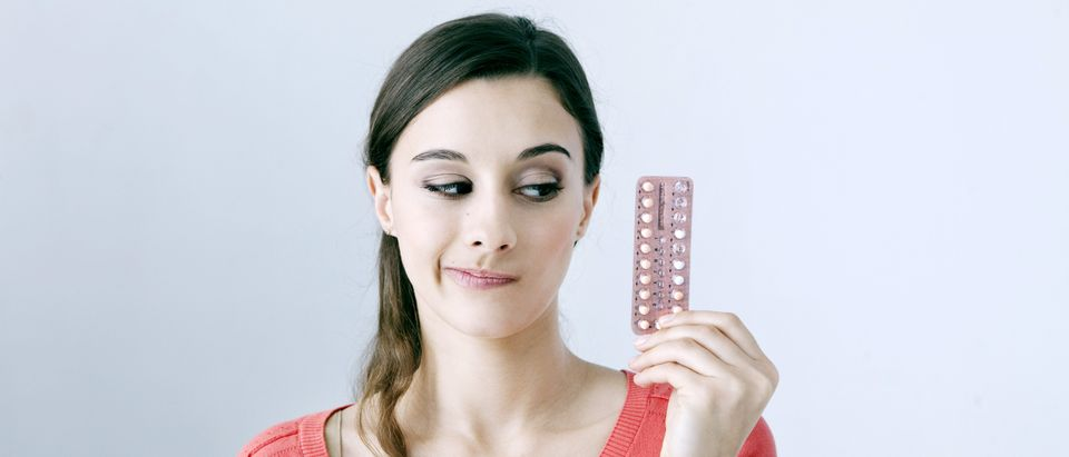Woman with contraceptive pills. (Shutterstock)