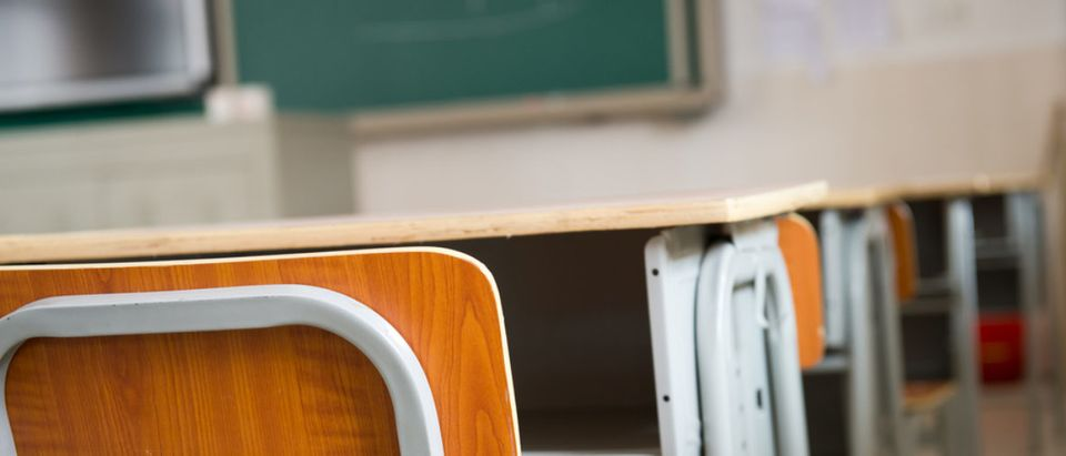 Pictured is an empty classroom with chairs and desks. (Shutterstock/hxdbzxy)