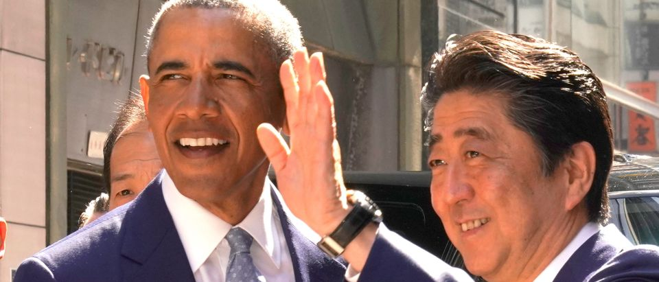 Former U.S. President Barack Obama and Japanese Prime Minister Shinzo Abe pose for photographers in front of Japanese Sushi restaurant in Tokyo's Ginza shopping district