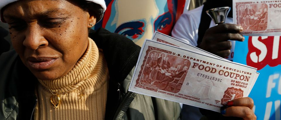 Protesters hold replicas of food stamps during a rally in support of higher pay for low-wage earners outside the National Air and Space Museum in Washington, December 5, 2013. REUTERS/Jonathan Ernst (UNITED STATES - Tags: BUSINESS EMPLOYMENT CIVIL UNREST FOOD SOCIETY)
