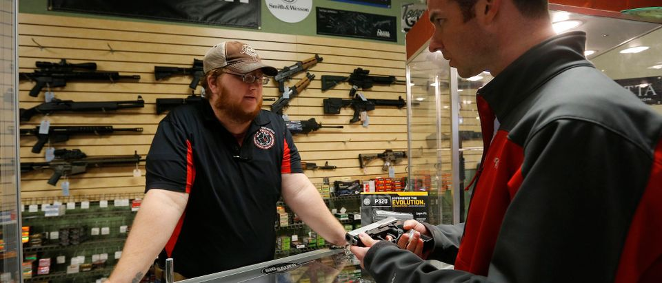 Metro Shooting Supplies' employee Chris Cox speaks to Steve Christy about the purchase of a 9mm handgun in Bridgeton, Missouri, November 13, 2014. REUTERS/Jim Young