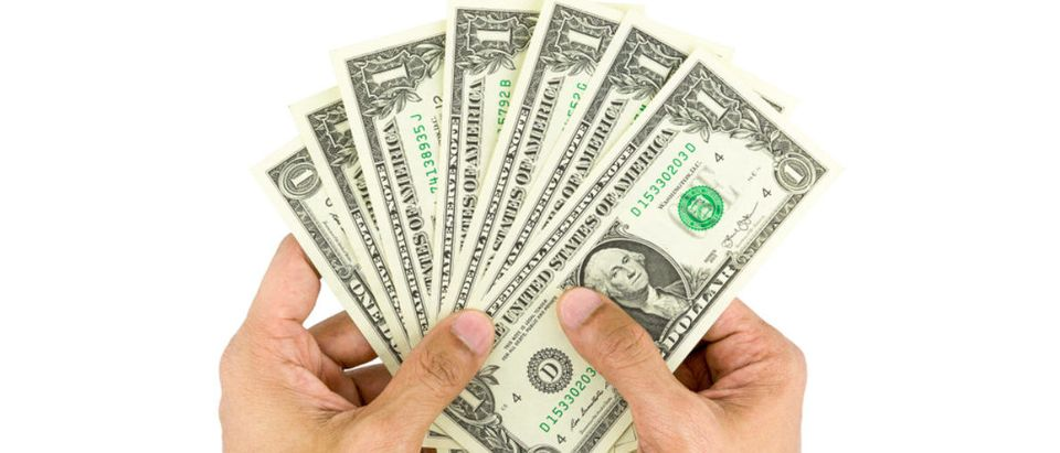 Hands hold dollar bills. (Shutterstock/dindumphoto) | UMich Funnels $11 Million Into Diversity