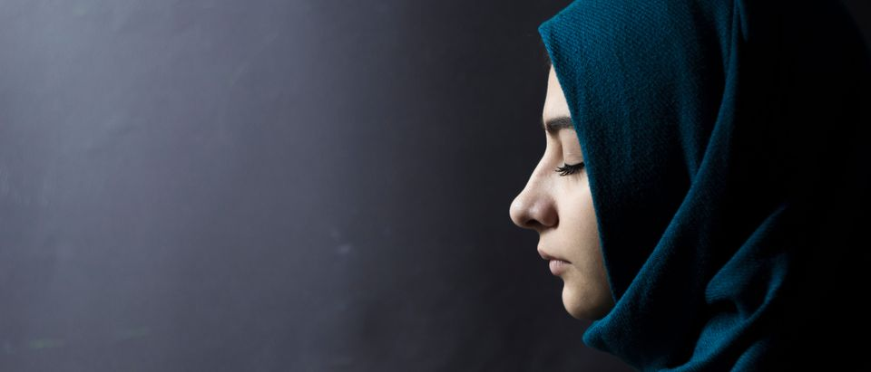 A Muslim woman with closed eyes, on a black background. Arab girl in hijab in profile. Shutterstock.