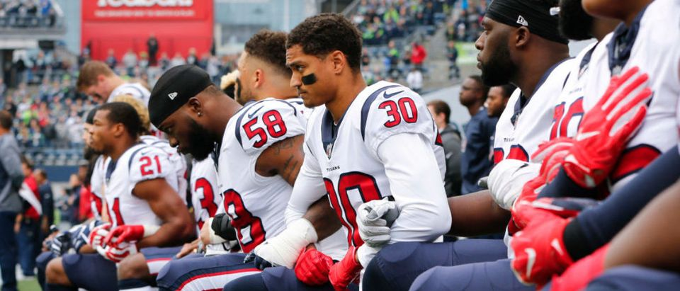 Members of the Houston Texans, including Kevin Johnson #30 and Lamarr Houston #58, kneel during the national anthem before the game at CenturyLink Field on October 29, 2017 in Seattle, Washington. (Photo by Jonathan Ferrey/Getty Images)