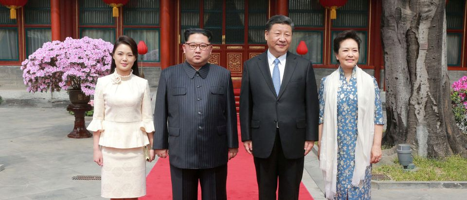 North Korean leader Kim Jong Un and wife Ri Sol Ju, and Chinese President Xi Jinping and wife Peng Liyuan pose for a photo