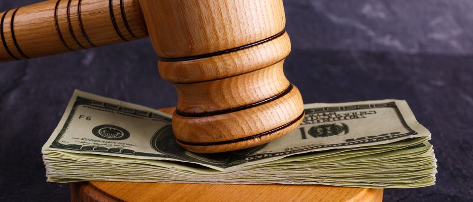 Money between the judge's hammer and the stand close-up on a stone background. (Shutterstock)