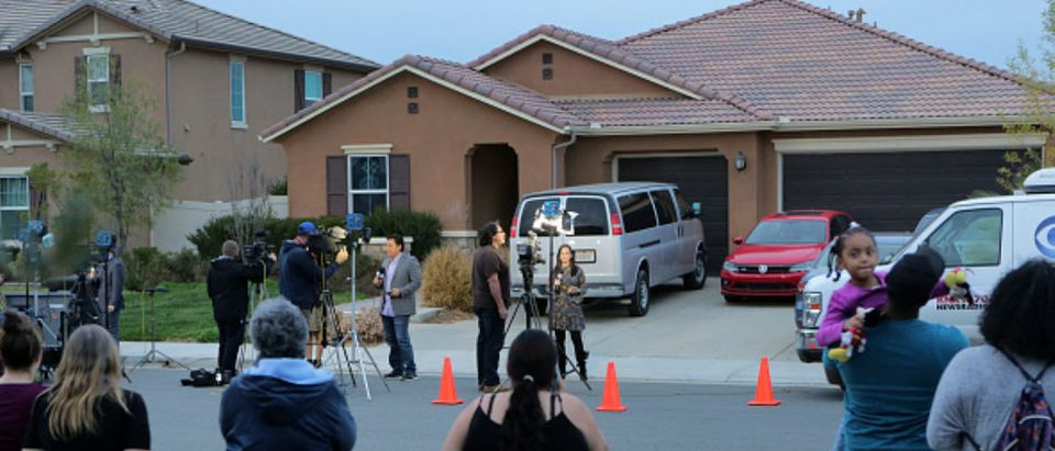 Perris, California, residents watch as media gather in front of 160 Muir Woods Road from where authorities rescued 13 malnourished children held captive by their parents. David Allen Turpin and Louise Anna Turpin have been arrested for torture after authorities said on Monday their 13 children were held captive in their home, with some shackled to beds in the dark. Authorities set bail at $9 million for the parents after a 17-year-old girl escaped the house on Sunday and called 911 using a cellphone found inside. / AFP PHOTO / BILL WECHTER/AFP/Getty Images
