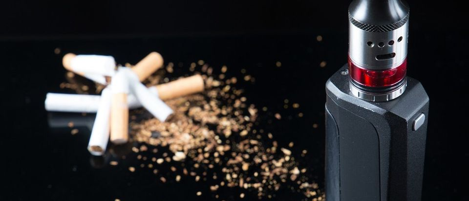 Pile of broken cigarettes with modern electronic cigarette. (Rain Ungert/Shutterstock)