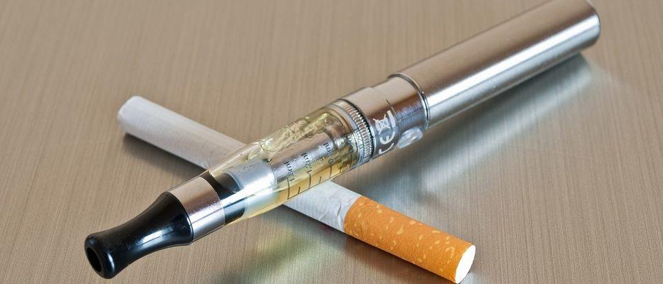 E-Cigarette with cigarette. (NeydtStock/Shutterstock)