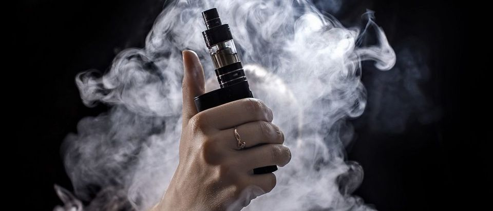 Girl soars on a black background vape. (SVETOV DMITRII/Shutterstock) | Paper Rips Florida Vaping Ban Amendment