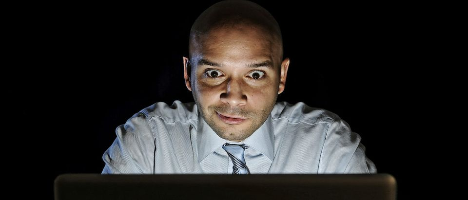 Young attractive businessman alone at night sitting at computer laptop watching porn or online gambling isolated on black background on internet chat addiction concept. (Shutterstock/Marcos Mesa Sam Wordley)