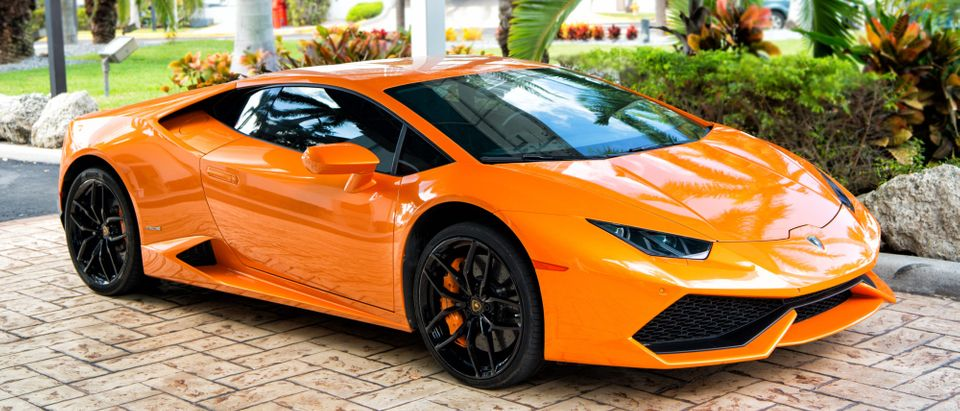 Supercar Lamborghini Aventador orange color parked next to Ocean drive at South beach at Miami, Florida. Shutterstock