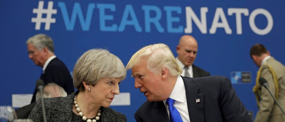 U.S. President Donald Trump speaks to Britain's Prime Minister Theresa May during in a working dinner meeting at the NATO headquarters during a NATO summit of heads of state and government in Brussels