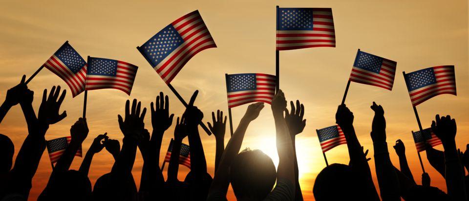 Group of People Waving American Flags in Back Lit. Shutterstock