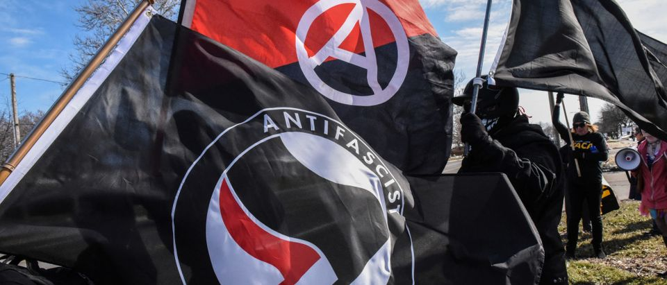 Members of the Great Lakes anti-fascist organization (Antifa) fly flags during a protest against the Alt-right outside a hotel in Warren, Michigan