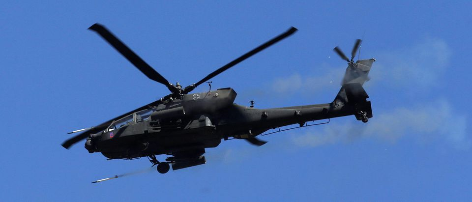 """A U.S. Apache helicopter fires as it takes part in the """"Saber Strike"""" NATO military exercise in Adazi"""