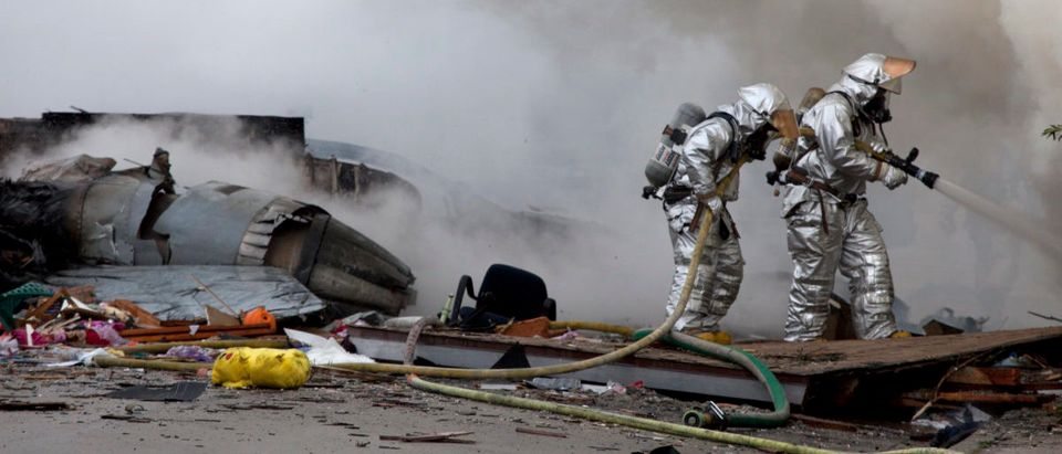 Firefighters battle flames next to the remains of a military jet that crashed into homes in San Diego