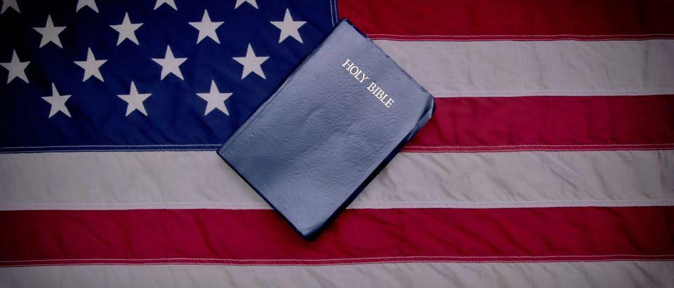 Bible And American Flag (Shutterstock/ ehrlif) | Navy Investigates Evangelizing Complaint