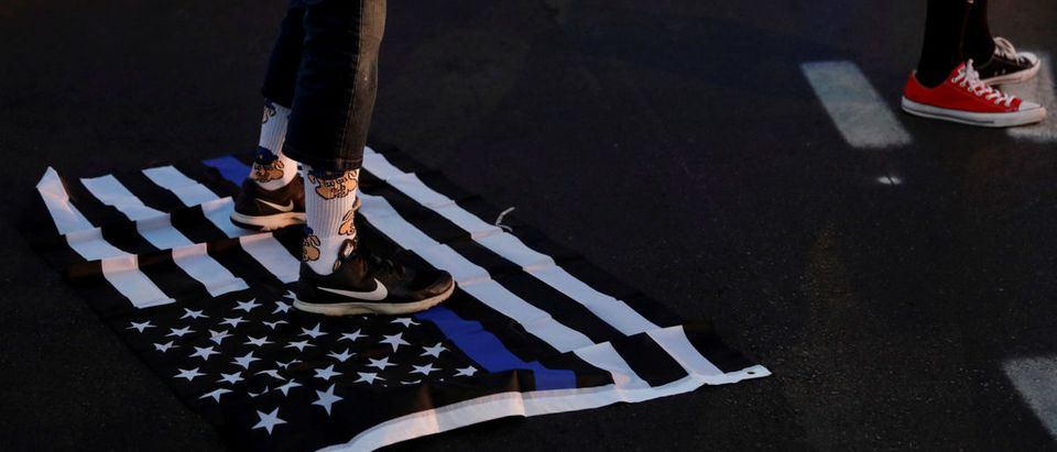 "A protester stands on a ""Blue Lives Matter"" flag after the not guilty verdict in the murder trial of Jason Stockley, a former St. Louis police officer, charged with the 2011 shooting of Anthony Lamar Smith, in St. Louis"