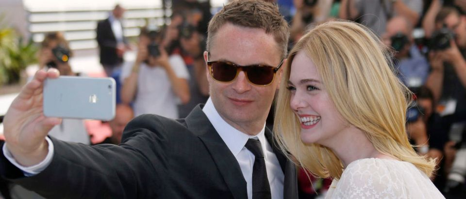 """Director Nicolas Winding Refn takes a selfie with cast member Elle Fanning as they pose during a photocall for the film """"The Neon Demon"""" in competition at the 69th Cannes Film Festival in Cannes"""