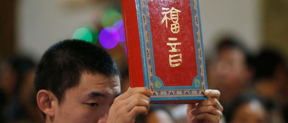 "A page boy holds up a bible during a Christmas mass at a Catholic church in Beijing December 24, 2014. Christmas is not a traditional festival in China but is growing in popularity, especially in more metropolitan areas where young people go out to celebrate, give gifts and decorate their homes. The words on the cover read, ""gospel"". REUTERS/Kim Kyung-Hoon 