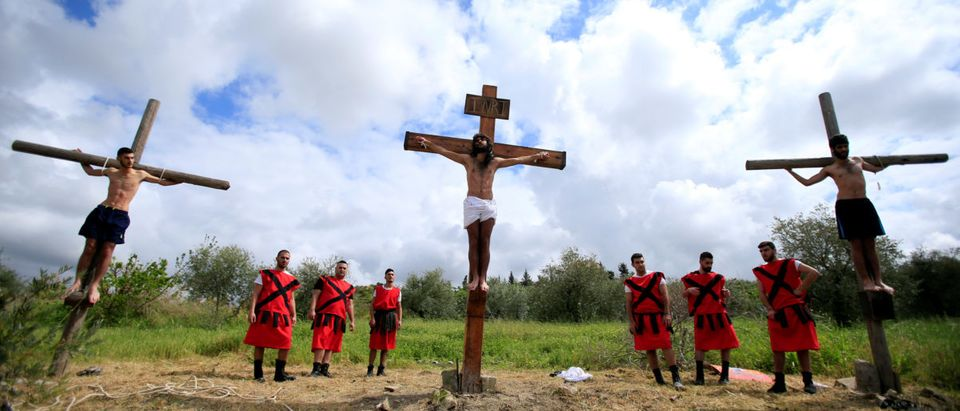 Christian men take part in a reenactment of the crucifixion of Jesus Christ on Good Friday in al-Qraya village