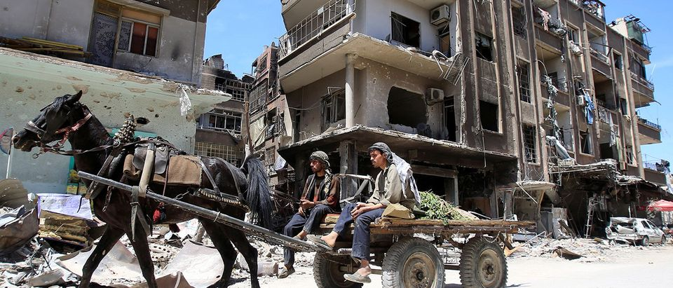 People ride a horse along a damaged street at the city of Douma in Damascus
