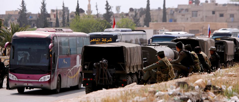 Buses carry rebels and their families who left Douma, at the entrance of Wafideen camp in Damascus