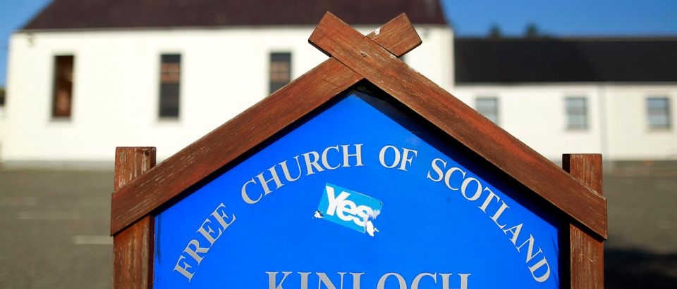 """A """"Yes"""" campaign sticker is stuck to a church sign on the Isle of Lewis, in the Outer Hebrides of Scotland September 15, 2014. The referendum on Scottish independence will take place on September 18, when Scotland will vote whether or not to end the 307-year-old union with the rest of the United Kingdom. REUTERS/Cathal McNaughton"""