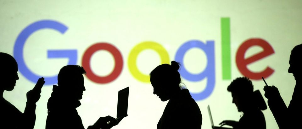 FILE PHOTO: Silhouettes of laptop and mobile device users are seen next to a screen projection of Google logo in this picture illustration