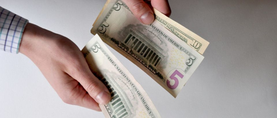 A man holds dollar bills. (Shutterstock/Tatiana Kasatkina)